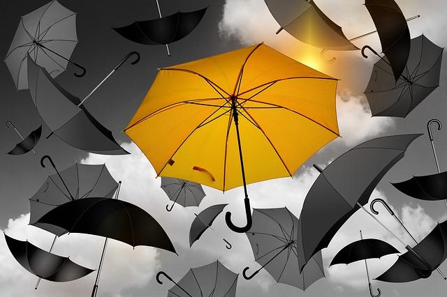 ombrello giallo in mezzo ad ombrelli grigi, la diversità